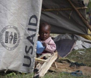 A child sits in a makeshift tent in Kanyaruchinya IDP camp outside of Goma, DRC